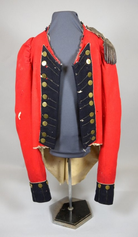 Red wool military coat owned by Major Campbell with black flannel, buttons in pairs, a rounded cut at the waist, and white piping.