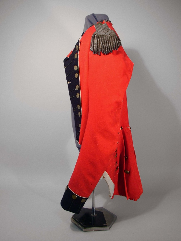 Side view of red wool military coat owned by Major Campbell with black flannel, buttons in pairs, a rounded cut at the waist, and white piping.