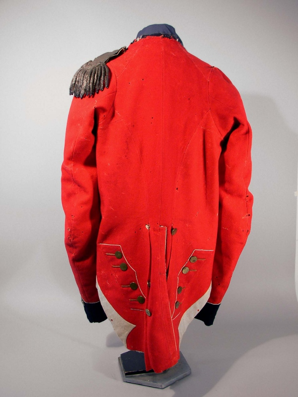Rear view of red wool military coat owned by Major Campbell with black flannel, buttons in pairs, a rounded cut at the waist, and white piping.