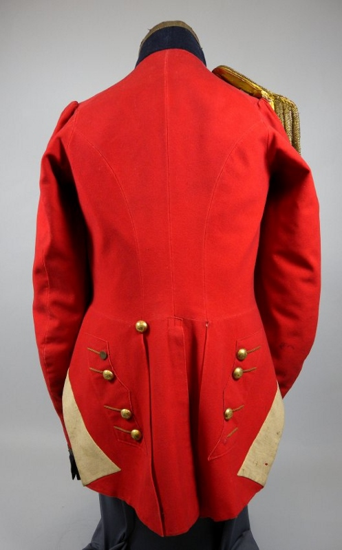 Rear view of military coat made with red wool broadcloth with black lace on dark-blue wool lapels, collar, and cuffs, worn by Captain John McMicking.