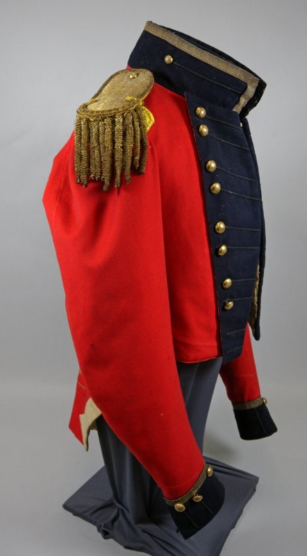 Side view of military coat made with red wool broadcloth with black lace on dark-blue wool lapels, collar, and cuffs, worn by Captain John McMicking.