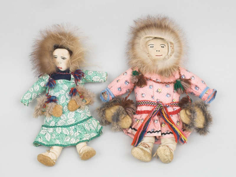 Two cloth dolls in full sets of northern clothing including parkas, dresses, stockings, and mukluks, created by young girls for a teacher.