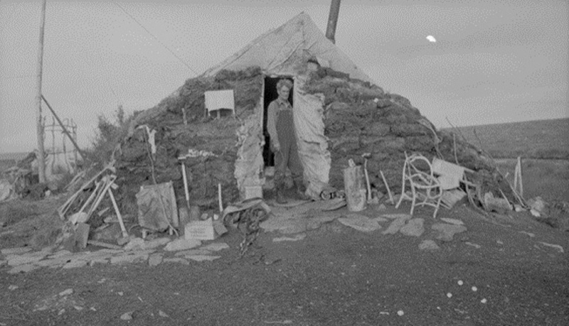 A male trapper stands in front of his makeshift shelter north of Great Slave Lake, Northwest Territories, 1943.
