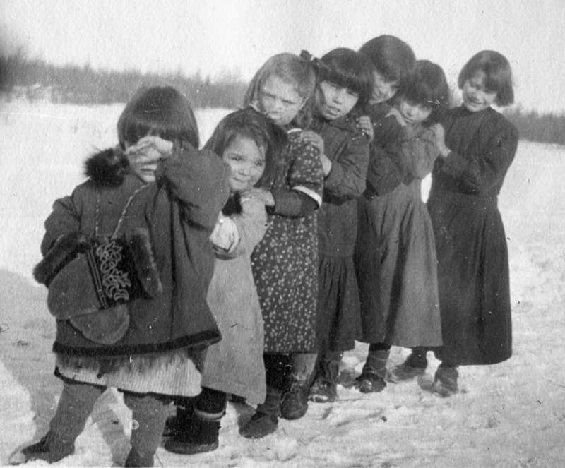 Seven children stand in a row at an Anglican residential school, 1920, one wearing distinctive traditional mittens.