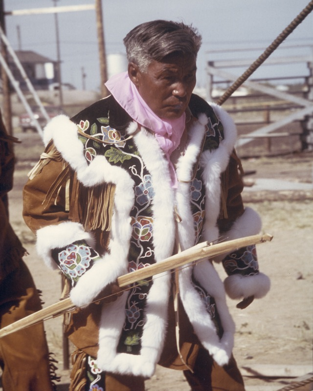 Chief Alexis Arrowmaker walks while wearing the vibrant beaded moose hide jacket at Treaty Day, 1975.