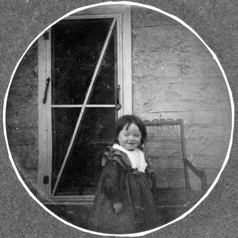 A young dark haired girl in dress stands in front of a babiche chair on a porch in front of a white screen door, 1900.