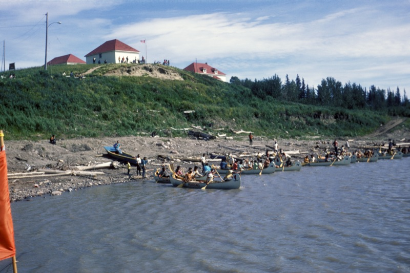 A rocky shore is full of canoes and paddlers waiting to begin a race down the Mackenzie River, 1970.