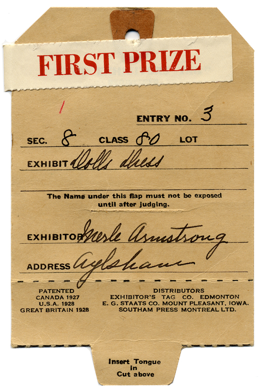 The entry tag for Merle's prize-winning doll dress, with first prize sticker.
