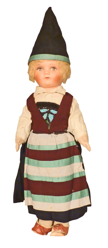 A blonde doll wearing traditional Swedish clothing, a pointy dark hat and dress of horizontal crimson bands.