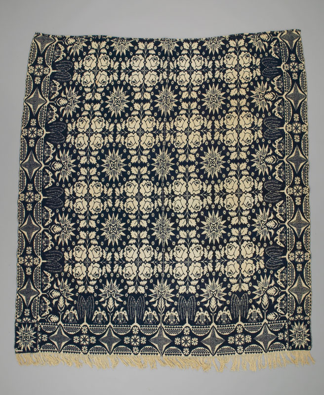 Rear view of a blue and white coverlet patterned with stars inside a grid of roses and bordered by eagles.