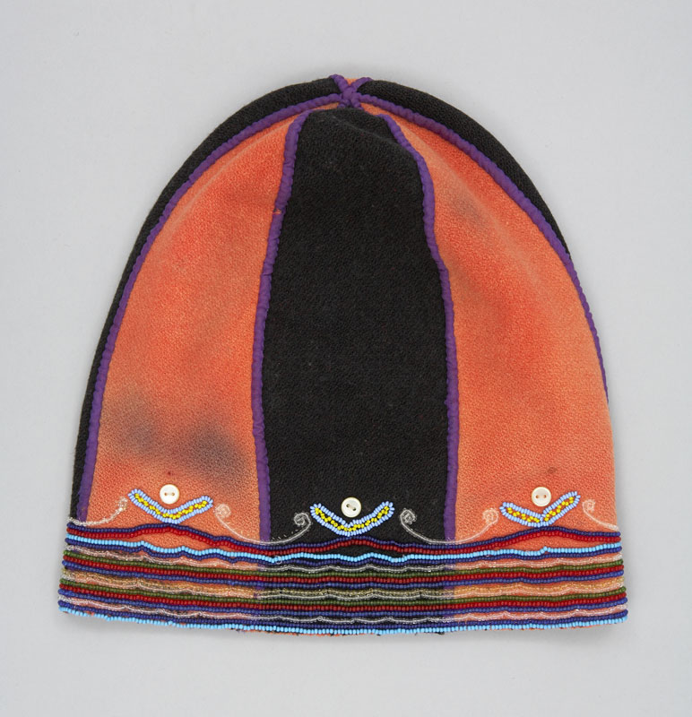 Rear view of domed hat made from red and black wool cloth with a rim of beaded double-curves.