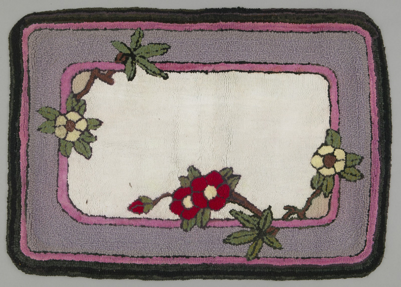 A rectangular hooked floor rug with thick gray border and pink lining, surrounding a cream coloured center and branching red and white flowers.
