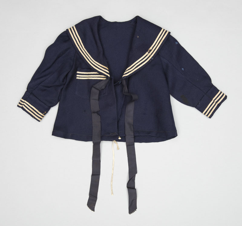 A long sleeved dark blue child's sailor jacket with crisp white trim, a mix of wool, cotton, and silk ribbon hanging down from the collar.