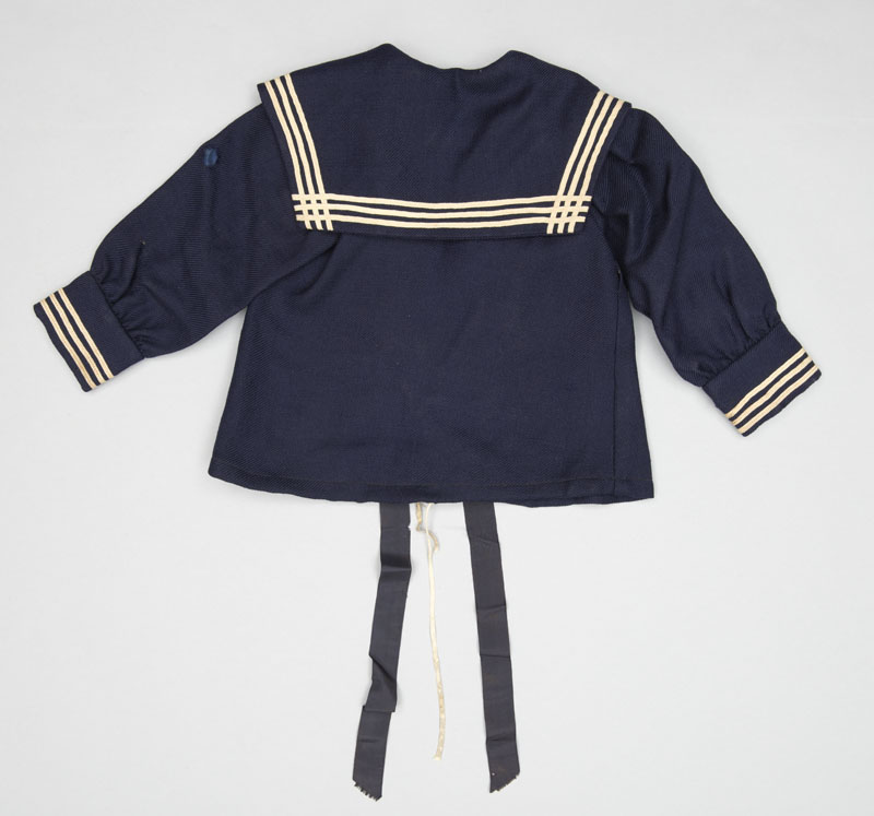 Rear view of a long sleeved dark blue child's sailor jacket with crisp white trim, a mix of wool, cotton, and silk ribbon hanging down from the collar.