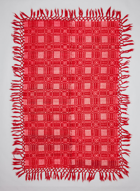 Rear view of a bright red rectangular coverlet with fringe and a stylized geometric pattern showing the intricate weave structure.